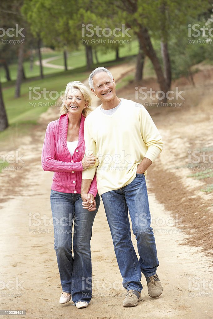 Elderly couple walking down a dirt path smiling royalty-free stock photo
