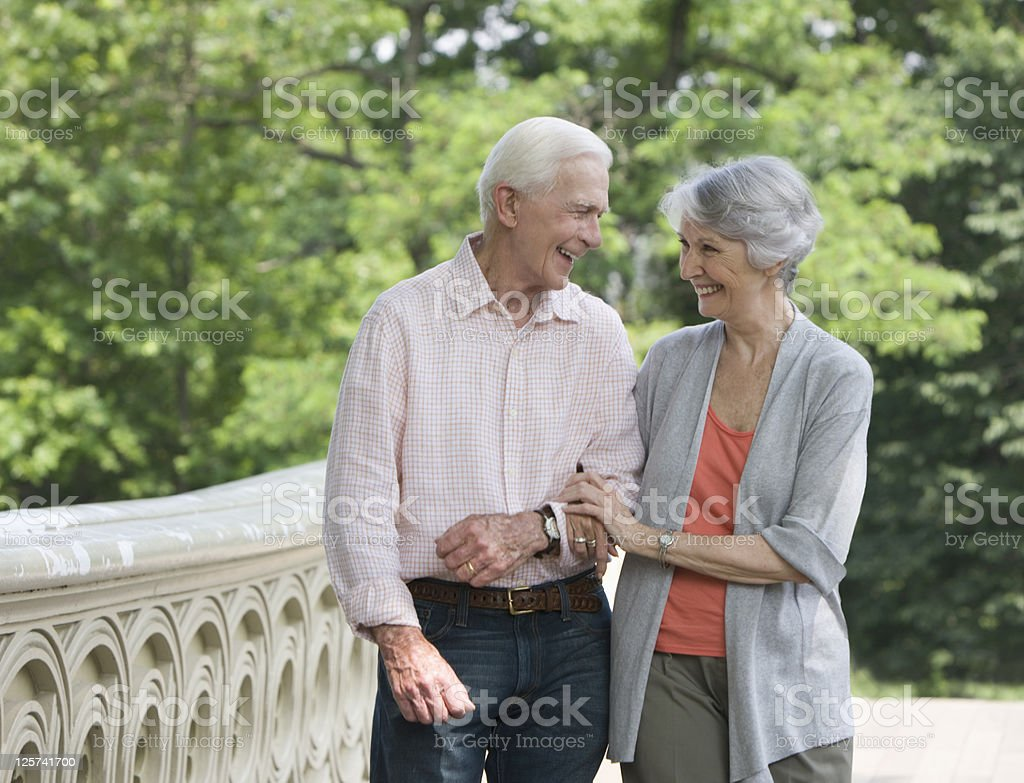 Elderly couple walking in the park smiling stock photo
