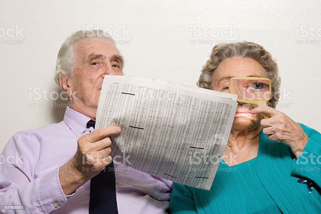 Elderly couple with newspaper stock photo
