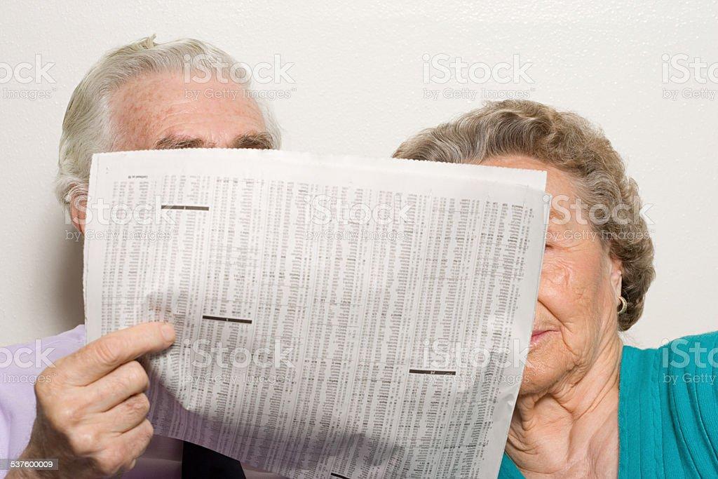 Elderly couple with newspaper stock photo