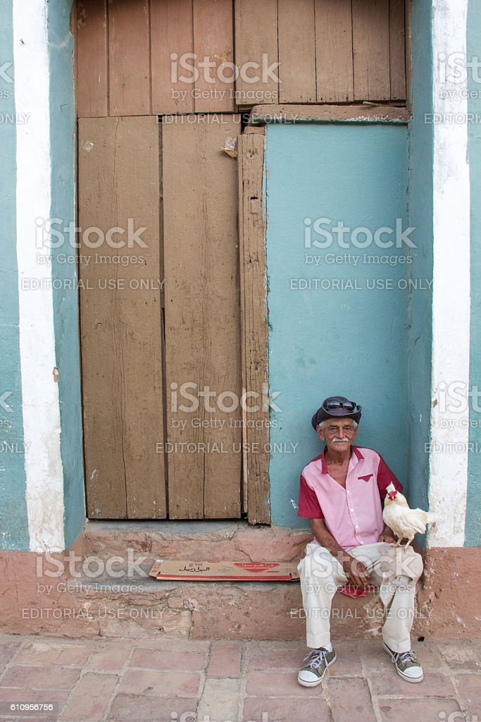 Elderly Cuban man with white hen seated outside door stock photo