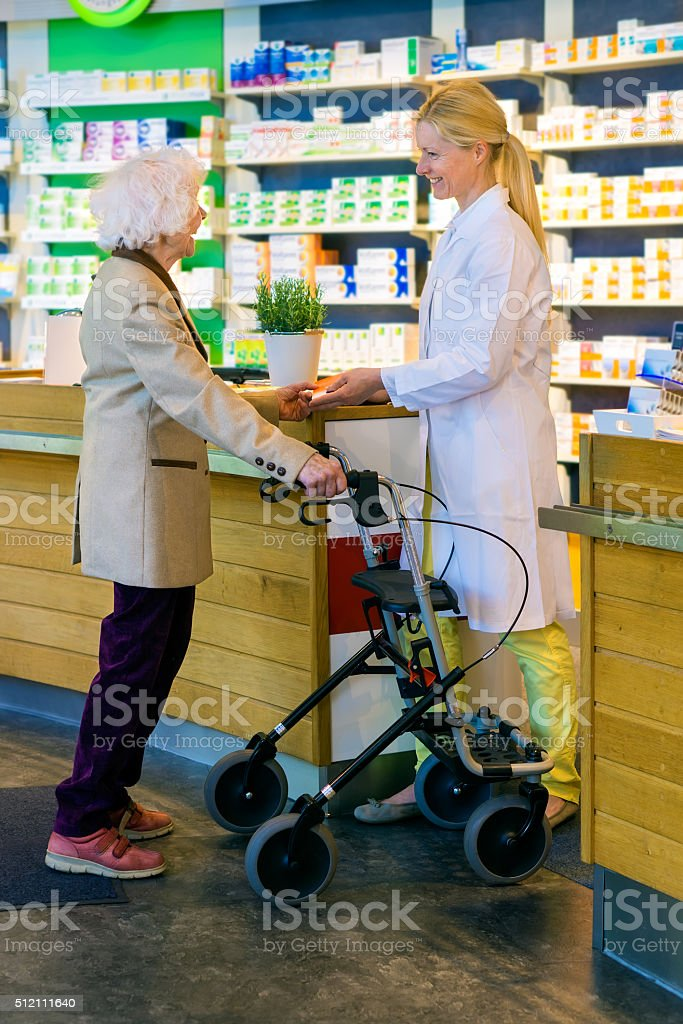 Elderly customer using walker with pharmacist. stock photo
