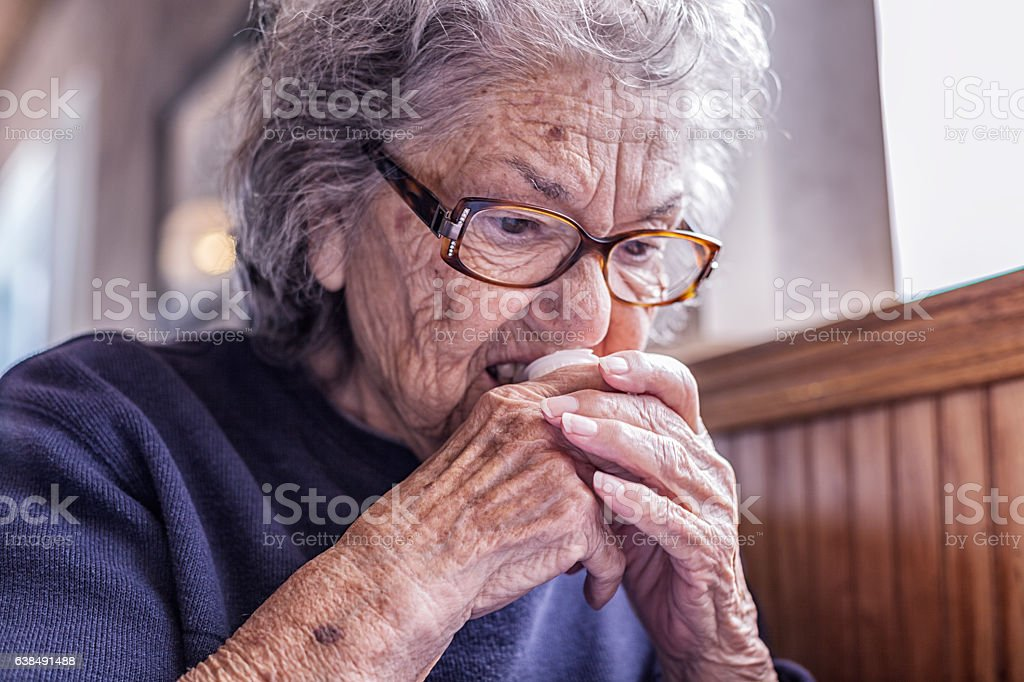 Elderly Dementia Woman Using Teeth to Open Coffee Cream Container stock photo