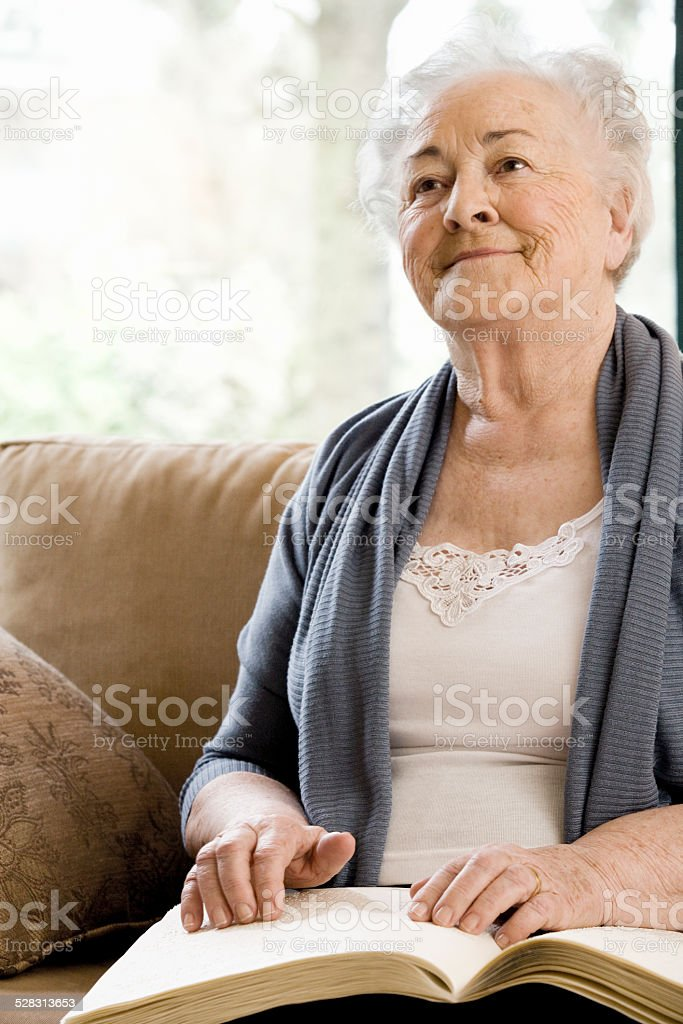 Elderly Disabled Woman Reading Book With Her Hands stock photo