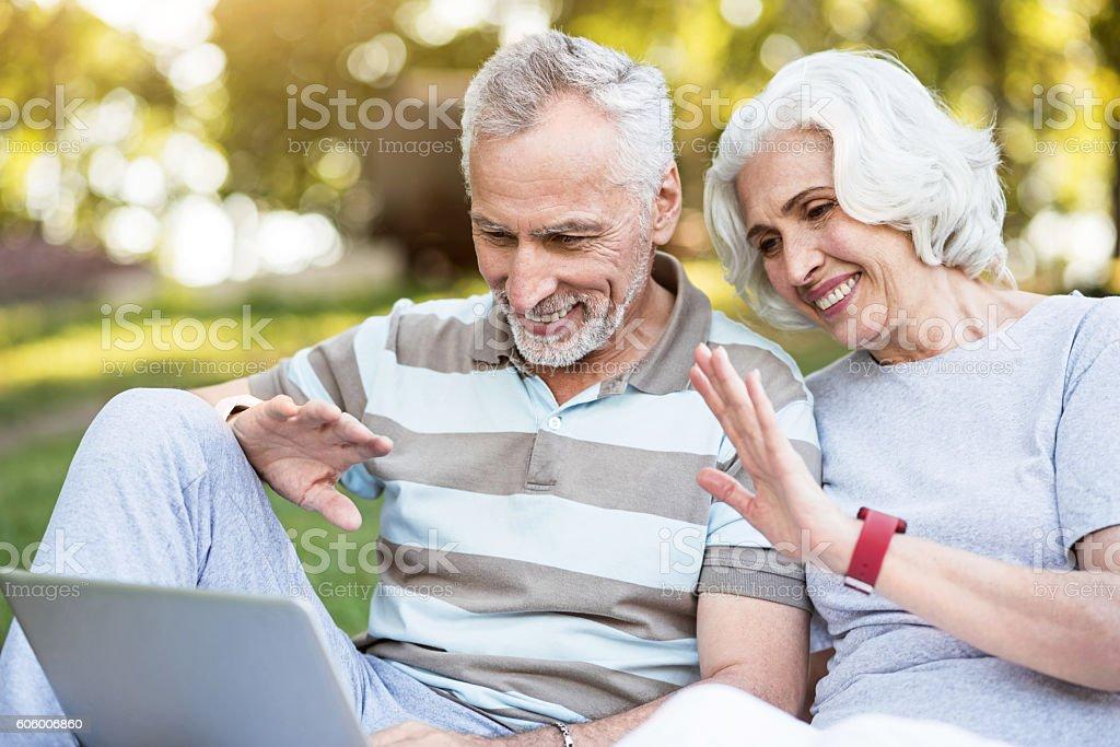 Elderly family using internet for communication sitting in a park stock photo