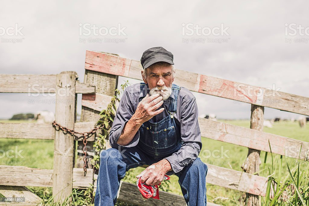 Elderly farm worker sitting relaxing stock photo