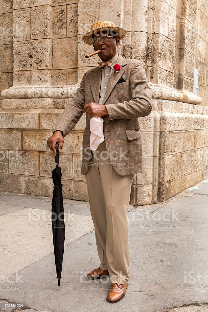 Elderly gentleman with cigar and umbrella in Havana, Cuba stock photo