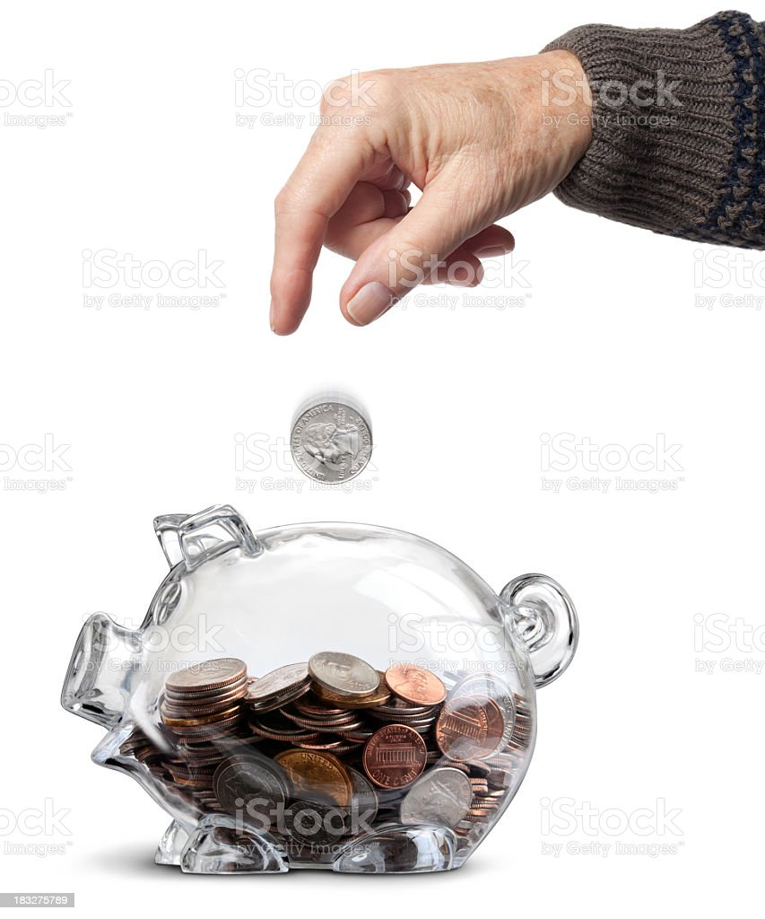 Elderly Hand Dropping Coin Into Clear Half-filled Piggy Bank Isolated royalty-free stock photo