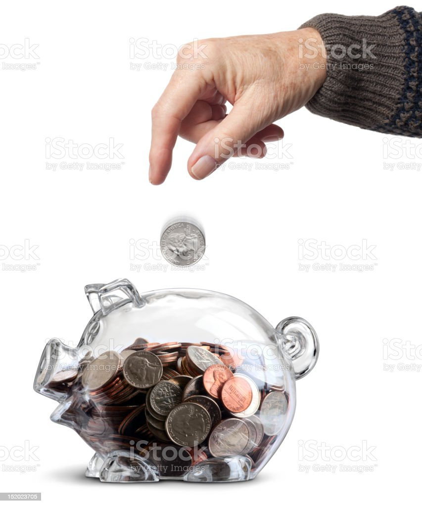 Elderly Hand Dropping Coin Into Clear Nearly Full Piggy Bank royalty-free stock photo