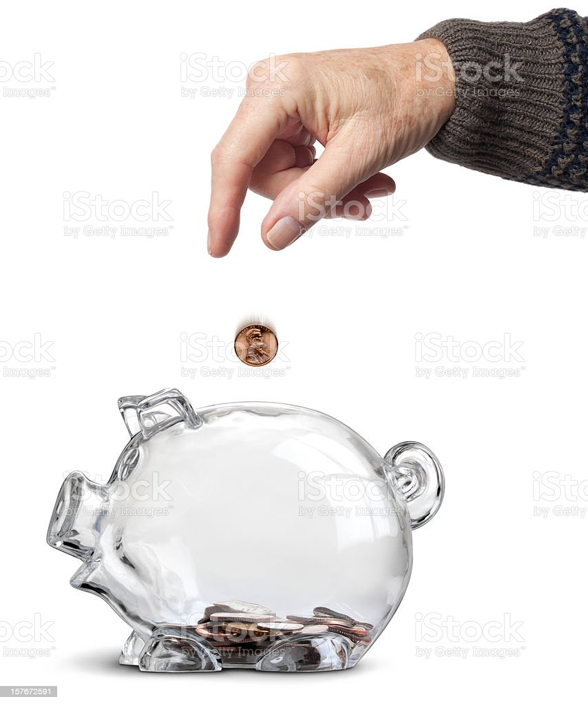 Elderly Hand Dropping Coins Into Almost Empty Piggy Bank Isolated royalty-free stock photo