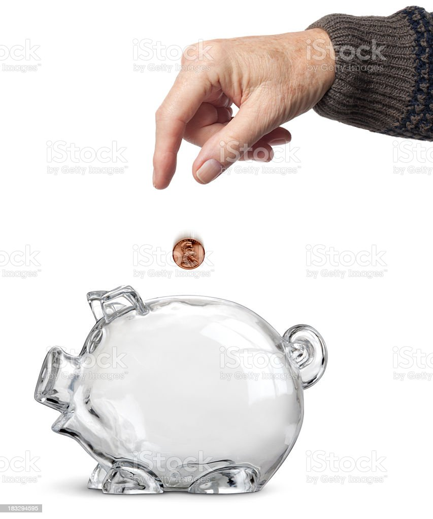 Elderly Hand Dropping Penny Into Clear Empty Piggy Bank Isolated royalty-free stock photo