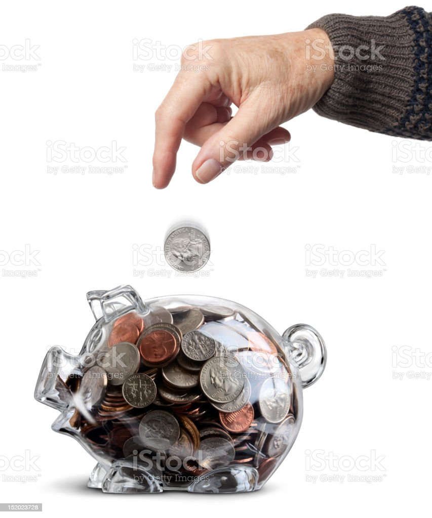 Elderly Hand Drops Coin Into Clear Full Piggy Bank Isolated royalty-free stock photo