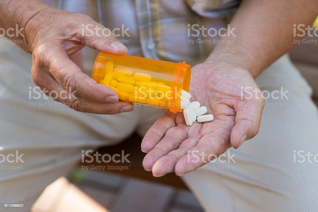 Elderly hand holds pills. stock photo