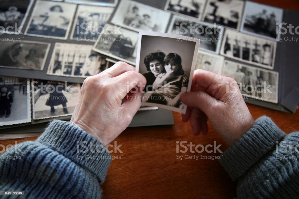 Elderly hands looking at old photos of self and family stock photo