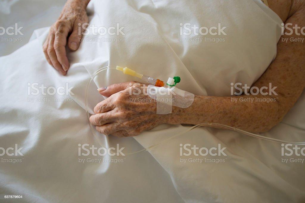 Elderly hands of sick woman in hospital stock photo