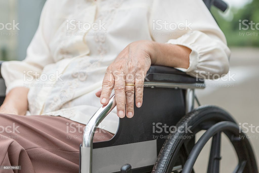 Elderly hands on a wheelchair. stock photo
