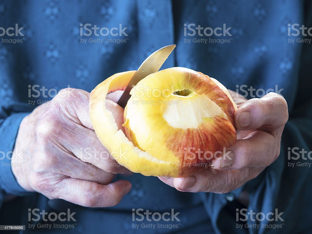 Elderly hands peeling an apple stock photo