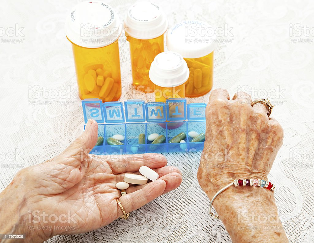 Elderly Hands Sorting Pills stock photo