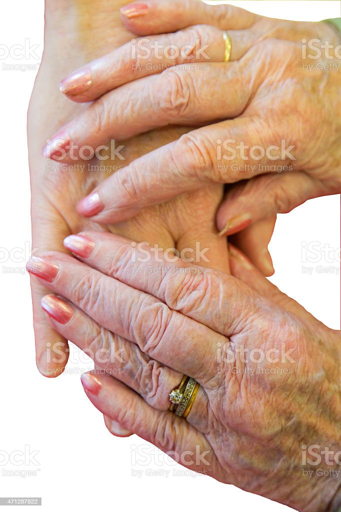 Elderly hands stretch over the hand of a loved one. stock photo