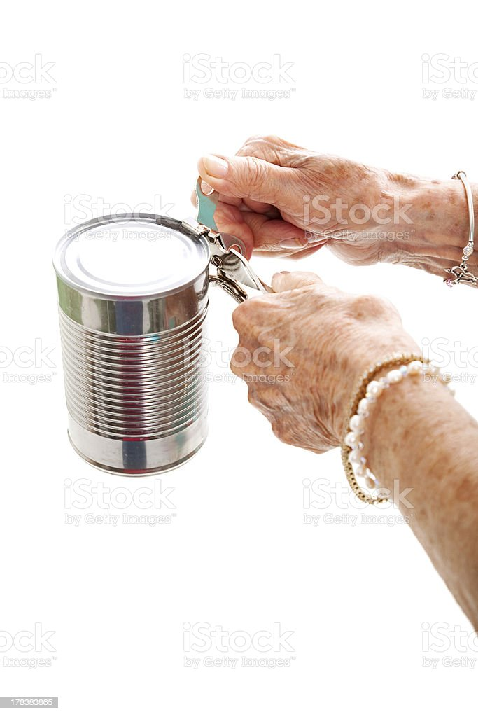 Elderly Hands Struggle with Can Opener stock photo