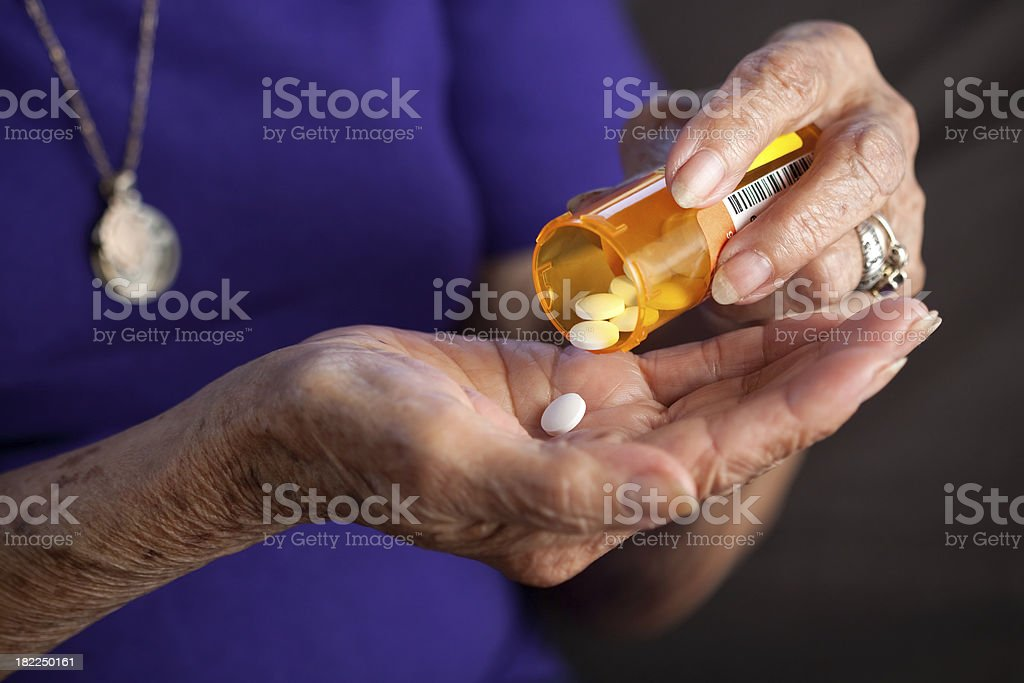 Elderly hands taking prescription medicine pill stock photo