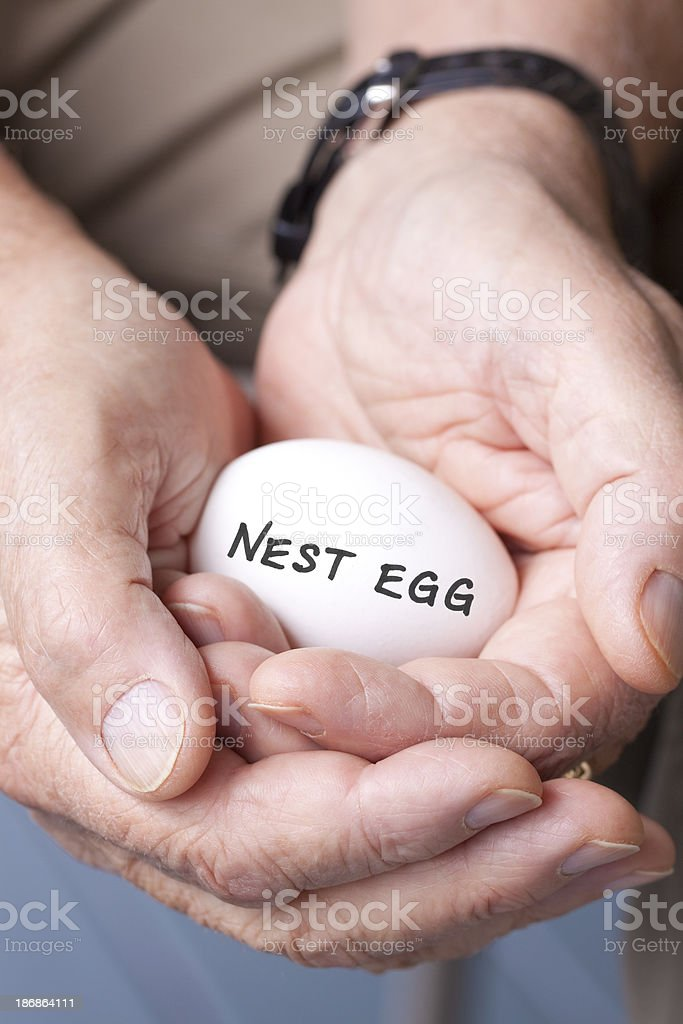 Elderly hands with nest egg stock photo