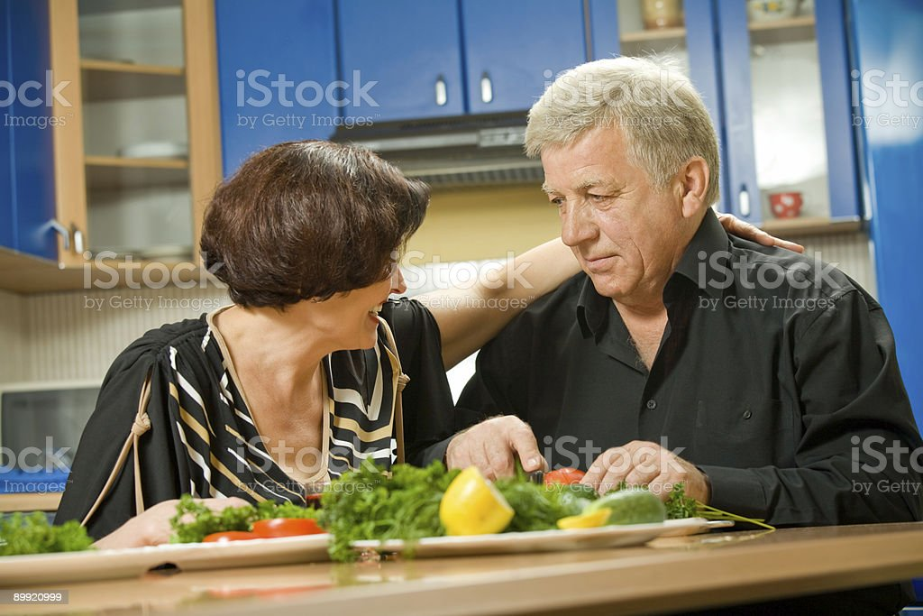 Elderly happy attractive smiling couple cooking at kitchen royalty-free stock photo