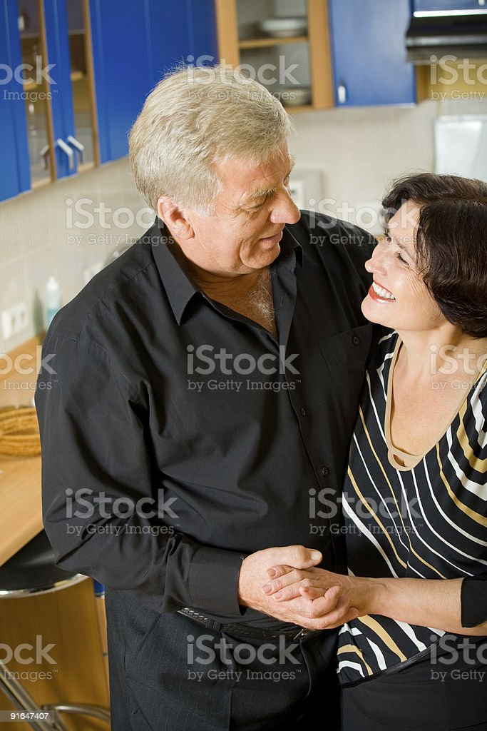 Elderly happy attractive smiling couple embracing at home royalty-free stock photo