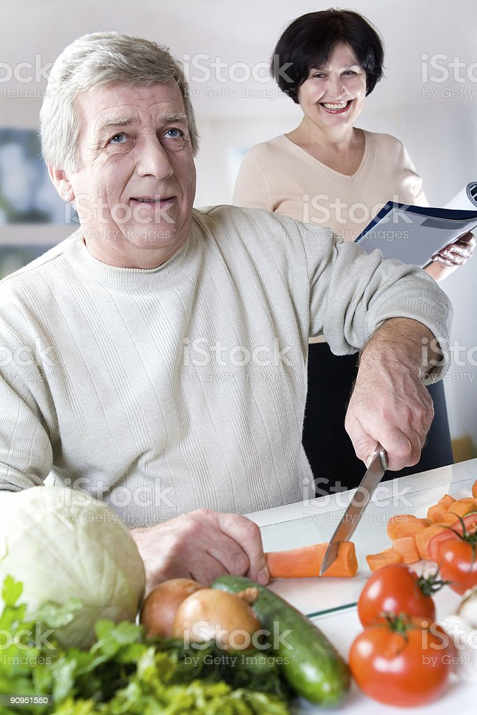 Elderly happy couple cooking at kitchen royalty-free stock photo
