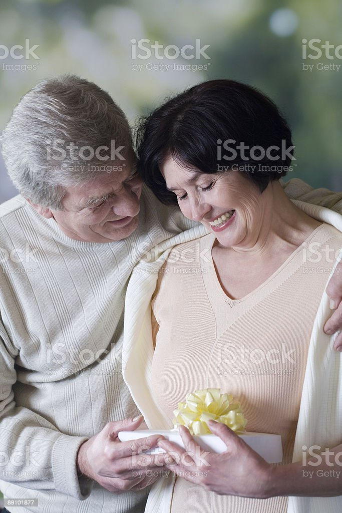 Elderly happy couple with gift box, smiling and embracing royalty-free stock photo