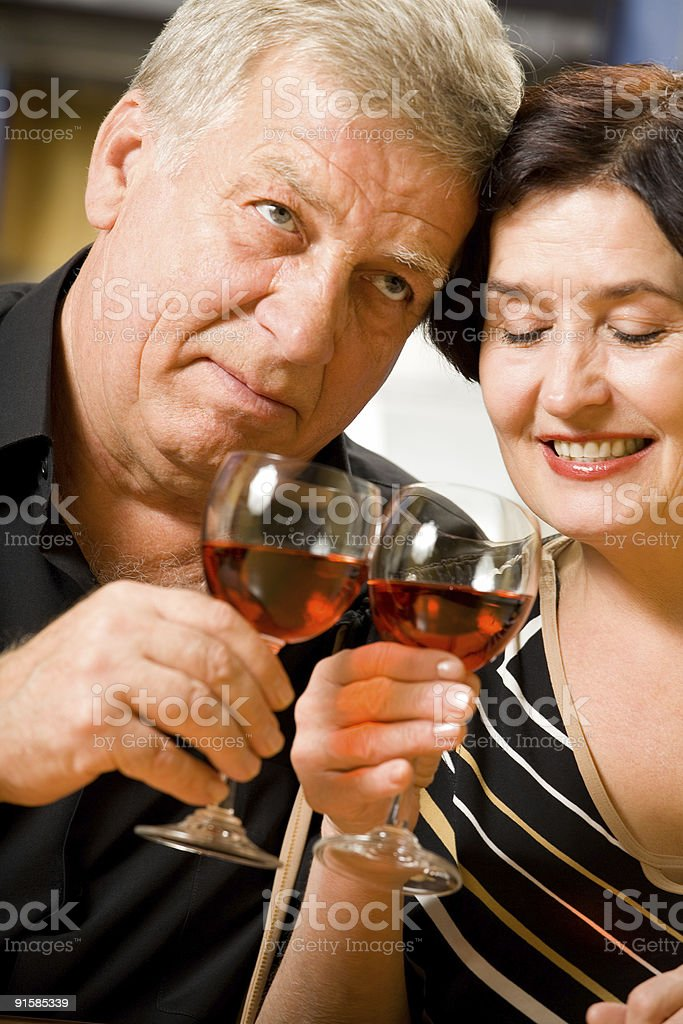 Elderly happy smiling couple celebrating with red wine at home royalty-free stock photo
