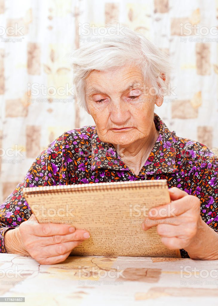 Elderly happy woman read something from the book royalty-free stock photo