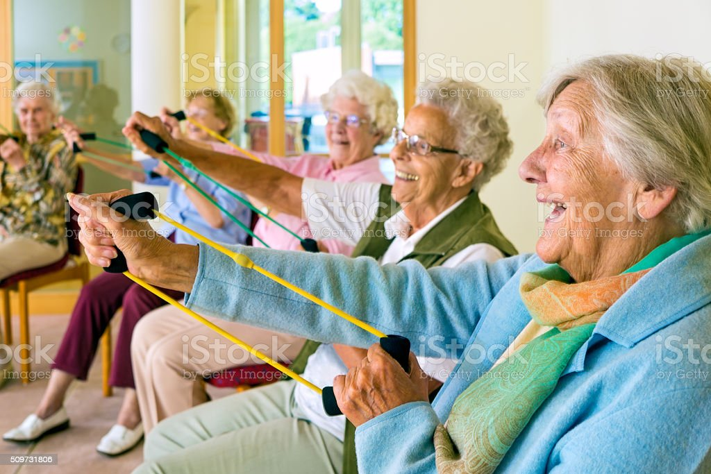 Elderly ladies exercising in a gym. stock photo