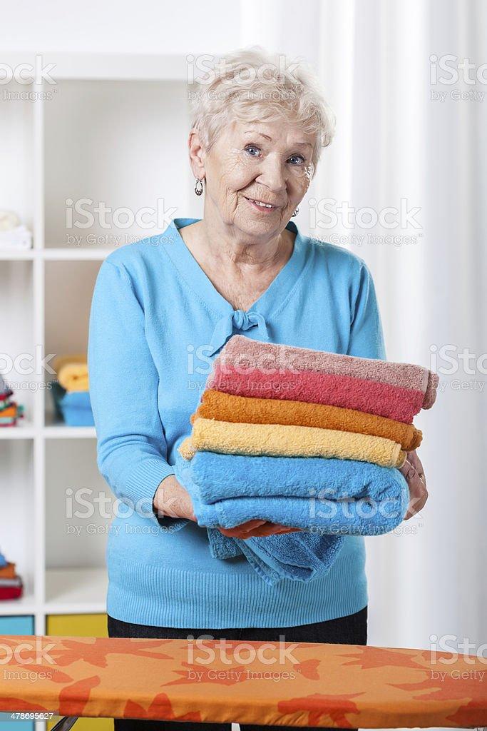 Elderly lady folding towels stock photo