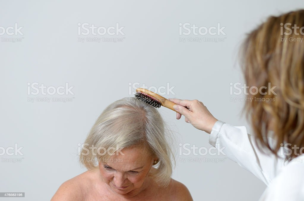 Elderly lady gets her hair combed stock photo