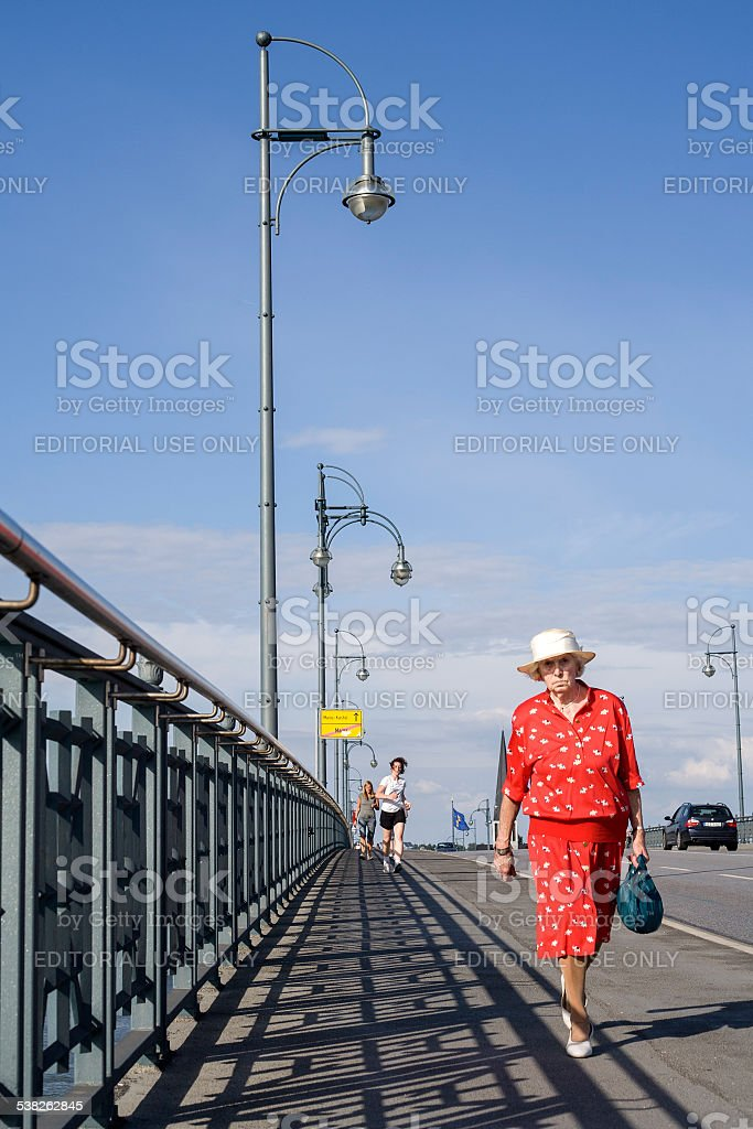 Elderly lady in a red dress stock photo