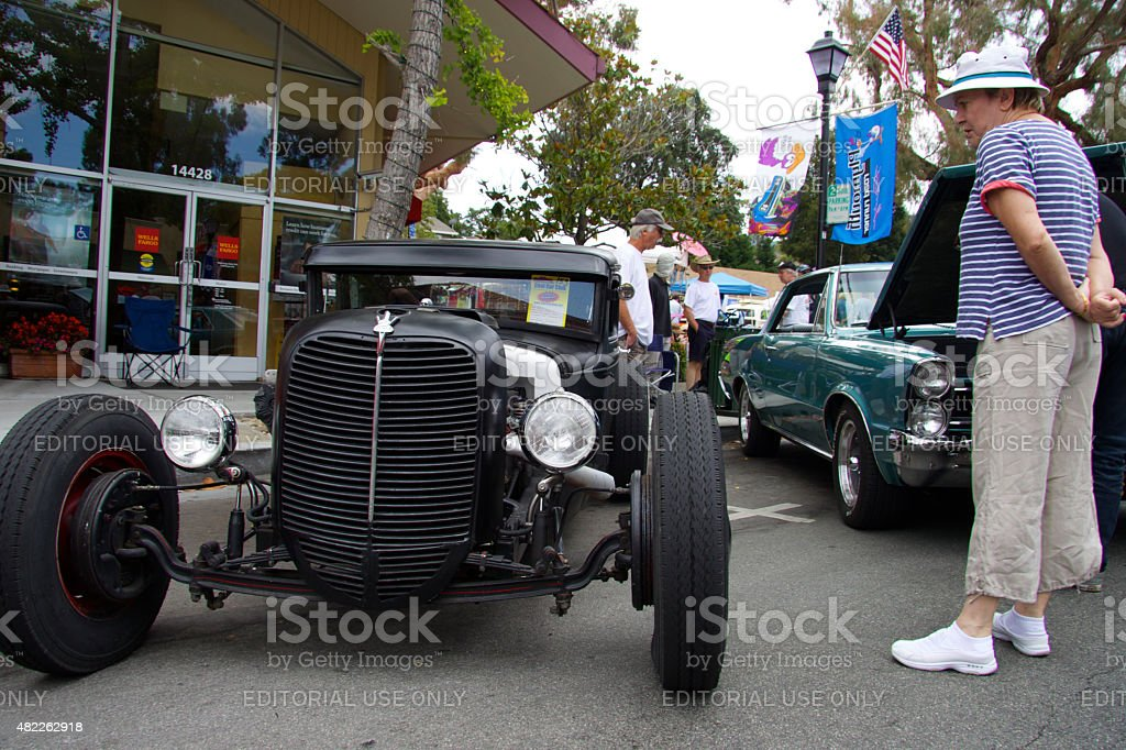 Elderly lady is considering Hot Rod (Ford Model A 1930) stock photo