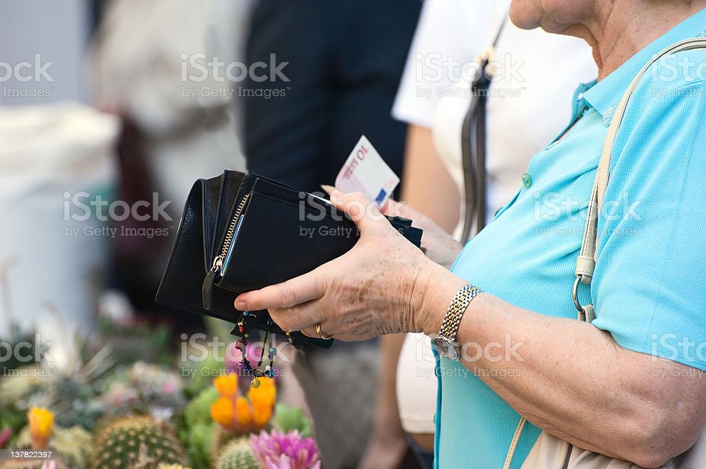 Elderly Lady is Paying the Florist. Color Image stock photo