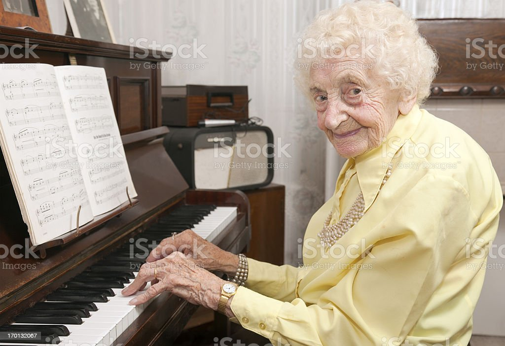 Elderly lady playing piano at home stock photo