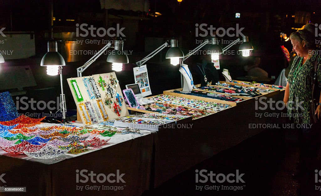 Elderly lady watching decorative objects made of glass stock photo