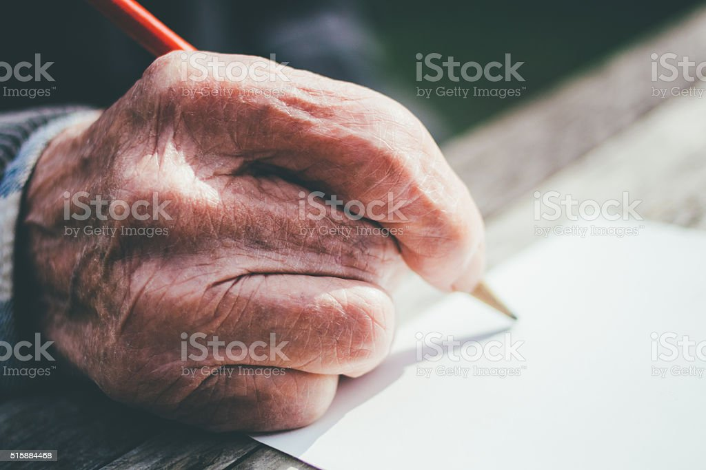 Elderly male hands on wooden table . writing on letter stock photo
