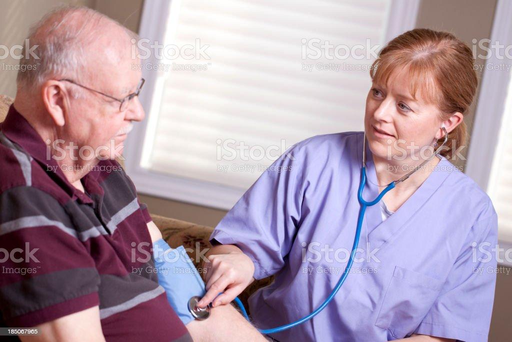 Elderly man and caregiver - stethescope royalty-free stock photo