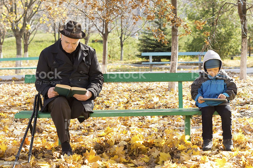 Elderly man and small boy sitting on a park bench stock photo