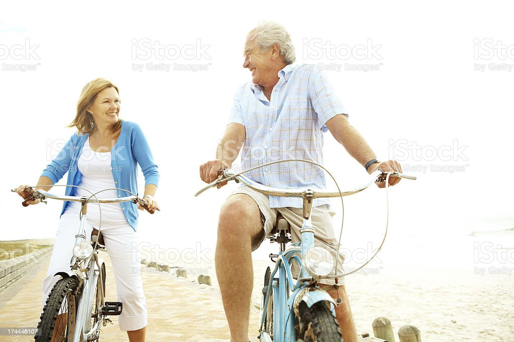 Elderly man and woman on bicycles stock photo