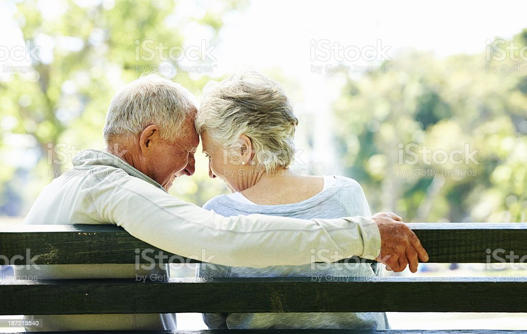 Elderly man and woman sit close on outdoor bench stock photo