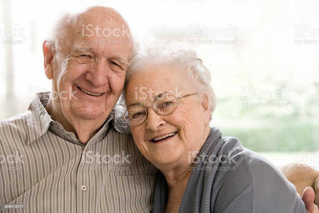 Elderly Man and Woman Sitting on Couch stock photo