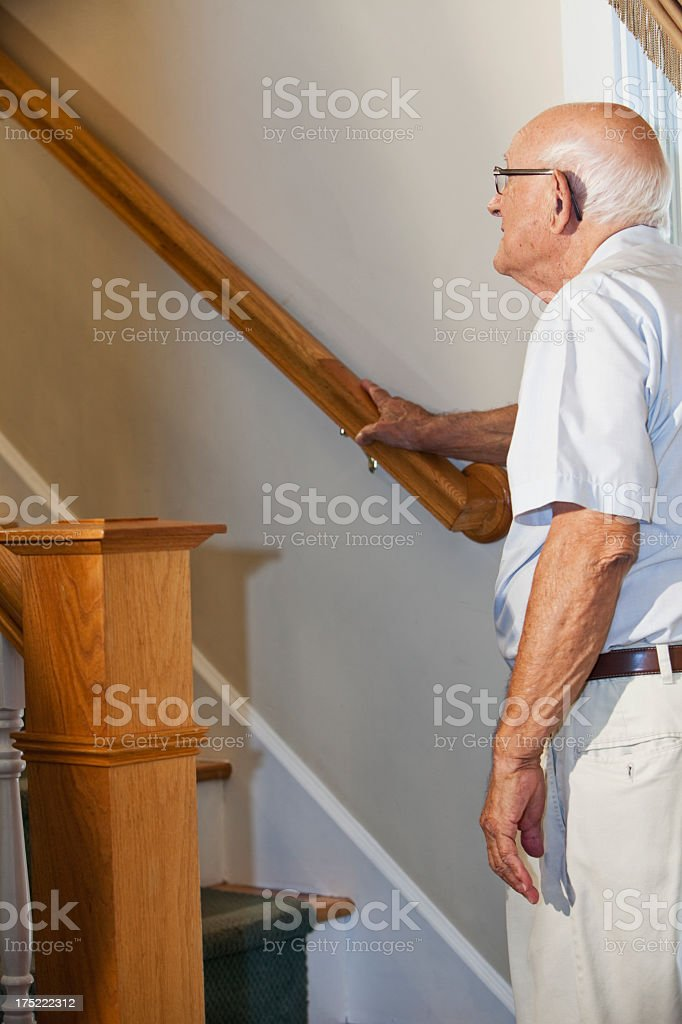 Elderly man at bottom of staircase looking up stock photo
