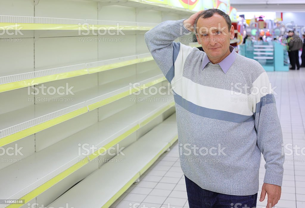Elderly man at empty shelves in shop royalty-free stock photo