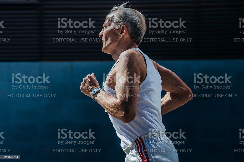 elderly man athlete running on a city street stock photo
