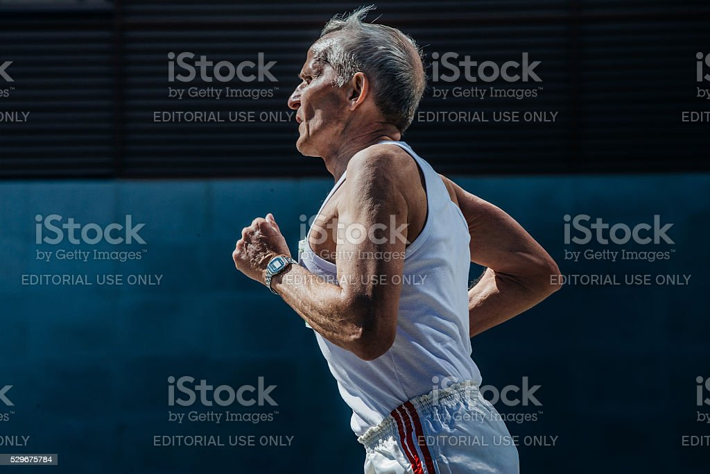elderly man athlete running on a city street stock photo